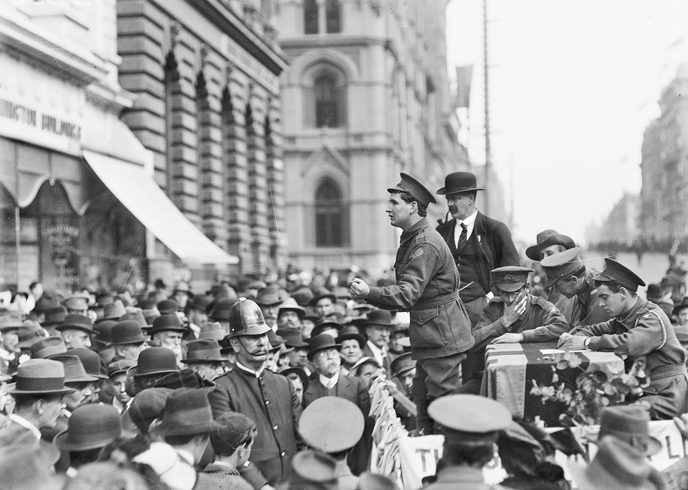 Black and white photo of soldiers campaigning in front of a crowd of men and a police officer.
