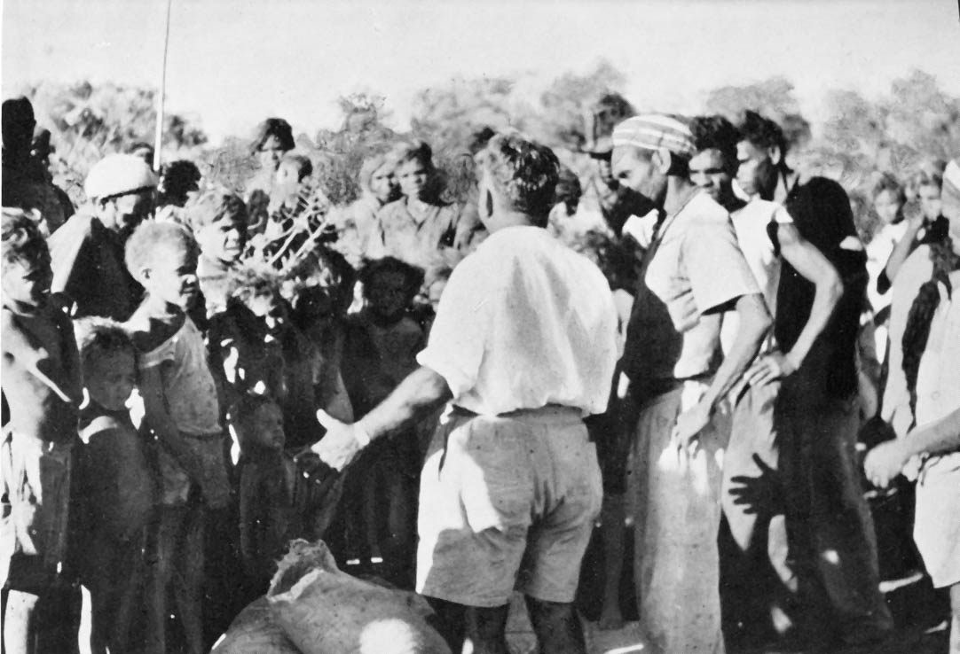 Black and white photo of a man talking to a large group of people.