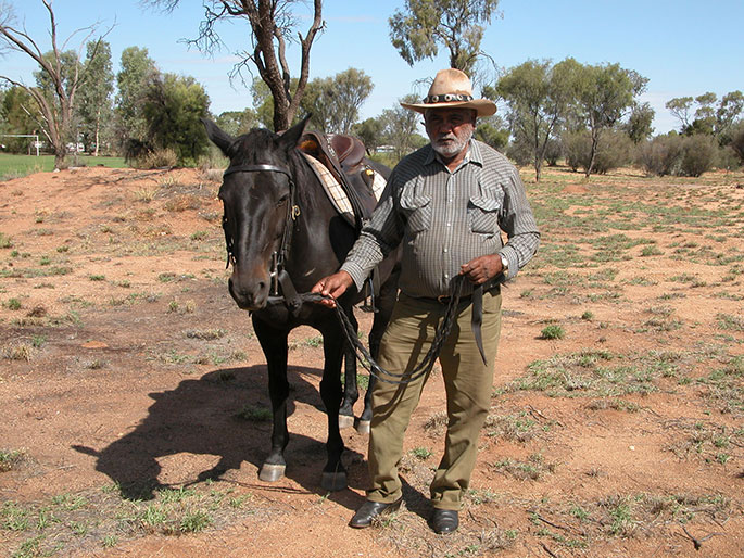 A man stands beside a horse, with gum trees and scrub in the background. - click to view larger image