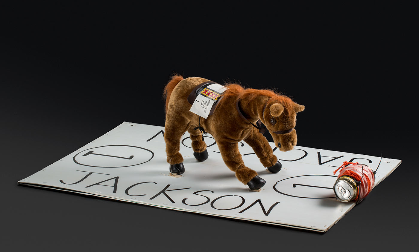 A soft toy horse stuck to a large piece of white card. A beer can with string rolled around it is attached to one end of the card.