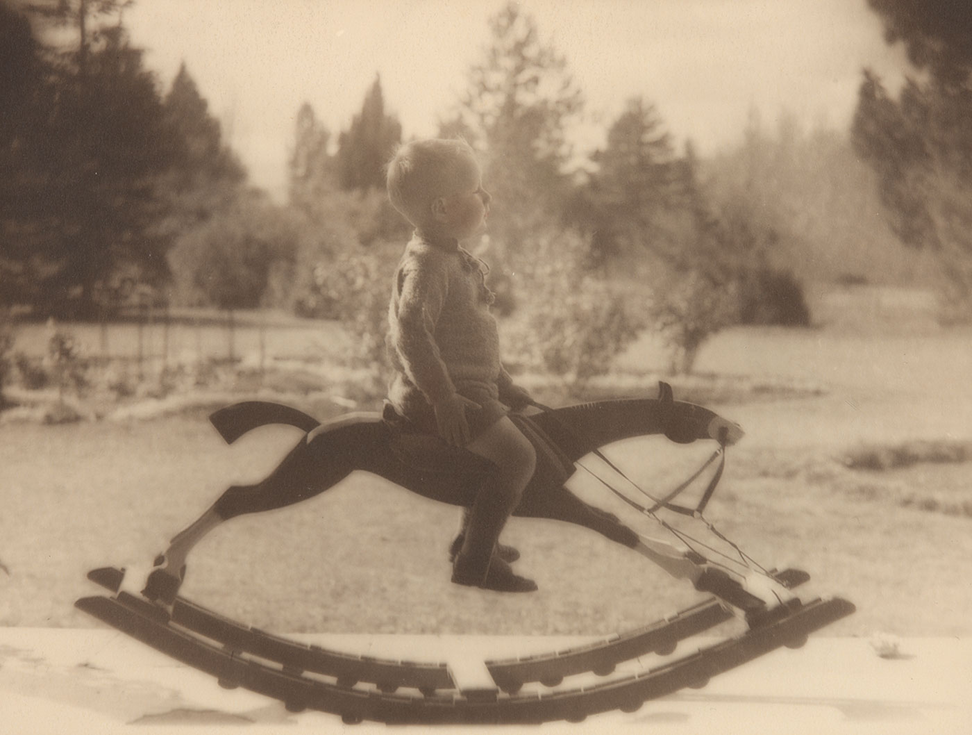 Black and white photo of a young boy on a rocking horse.