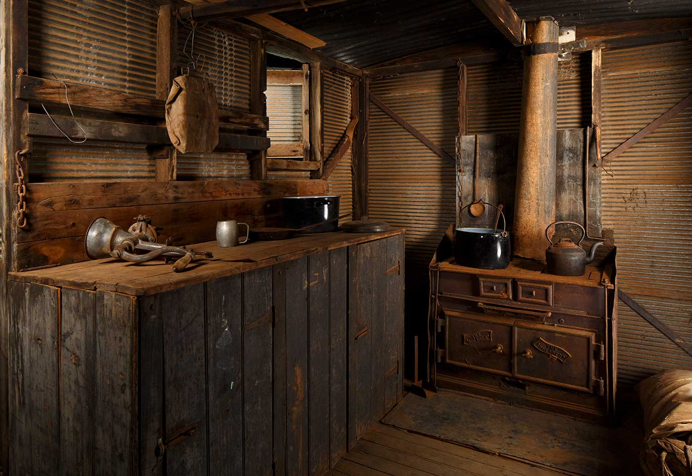 A cook's galley in the form of a metal-clad, timber and iron-framed box raised on wagon wheels. This view is of the front half of the galley showing the wood fired stove on the right and the galley bench on the left. - click to view larger image