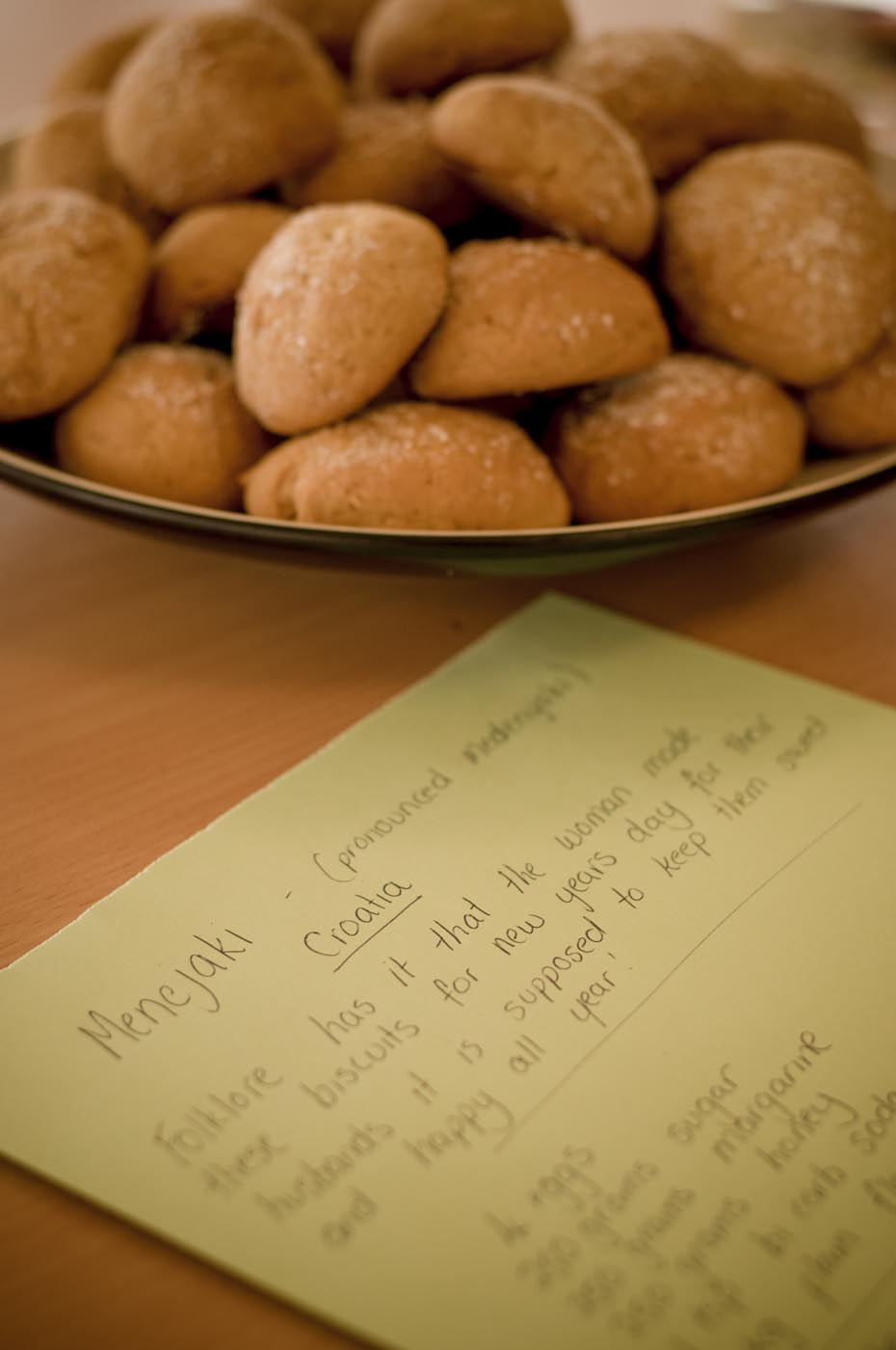 Photo showing a handwritten receipt for Menejaki, Croatian biscuits, with a bowl of the biscuits displayed above - click to view larger image