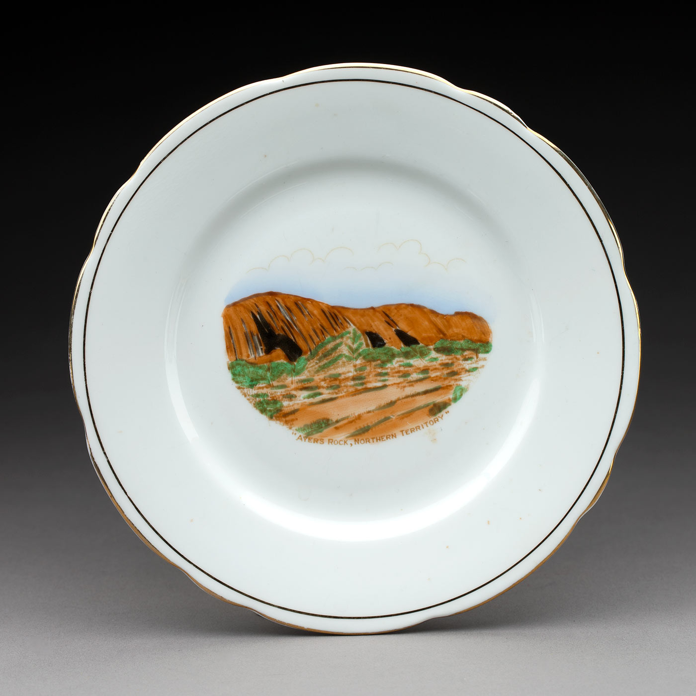 Painting of Uluru on a souvenir plate. - click to view larger image