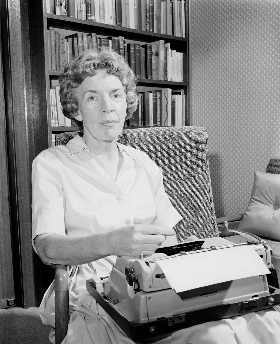 A black and white photograph of a woman sitting in an upholstered chair in front of a tall bookcase full of books. She has a portable typewriter on her lap and there is a sheet of paper in the typewriter platen. She is looking at the camera and resting her right hand on top of the typewriter. - click to view larger image