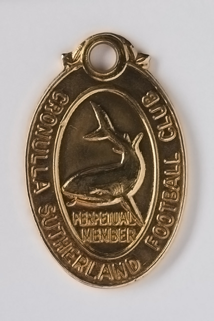 Front view of medallion which has a shark symbol in the centre and is inscribed with 'Perpetual Member Cronulla Sutherland Football Club'. - click to view larger image