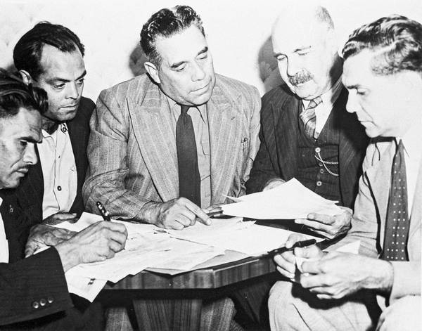 Black and white photo of a group of men in discussion over a table laden with official documents. - click to view larger image