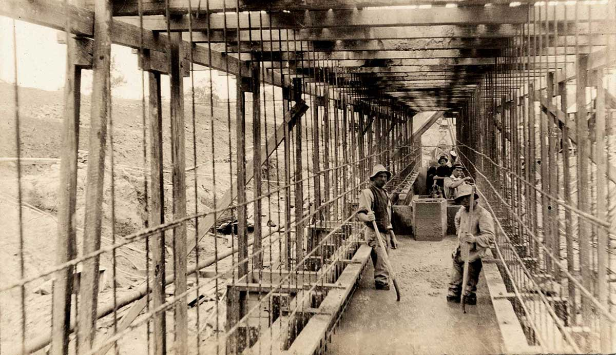 Black and white photograph of labourers standing in wet concrete on a construction site. - click to view larger image