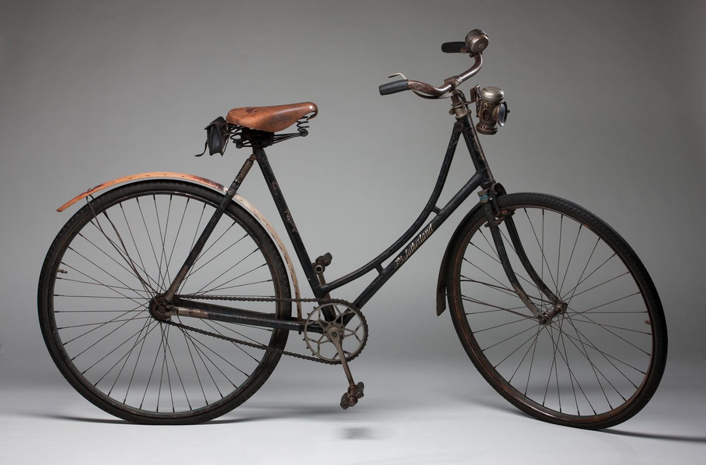 A ladies bicycle with a black painted metal frame, featuring a painted gold design on the front stem which reads 'The / SUTHERLAND / CYCLE / & MOTOR / WORKS / OPPOSITE / TOORAK STATION / MELBO[UR]NE. It has an oil lamp and a bell attached to the front handle bars and a tool/repair kit attached under the back of the seat. It has wooden mud guards, a steering lock for the front wheel, a front stirrup brake, a rear hand break and a leather saddle (seat) made by 'BROOKS'. A skip tooth chain wheel and pins hold the bottom bracket cups in position.