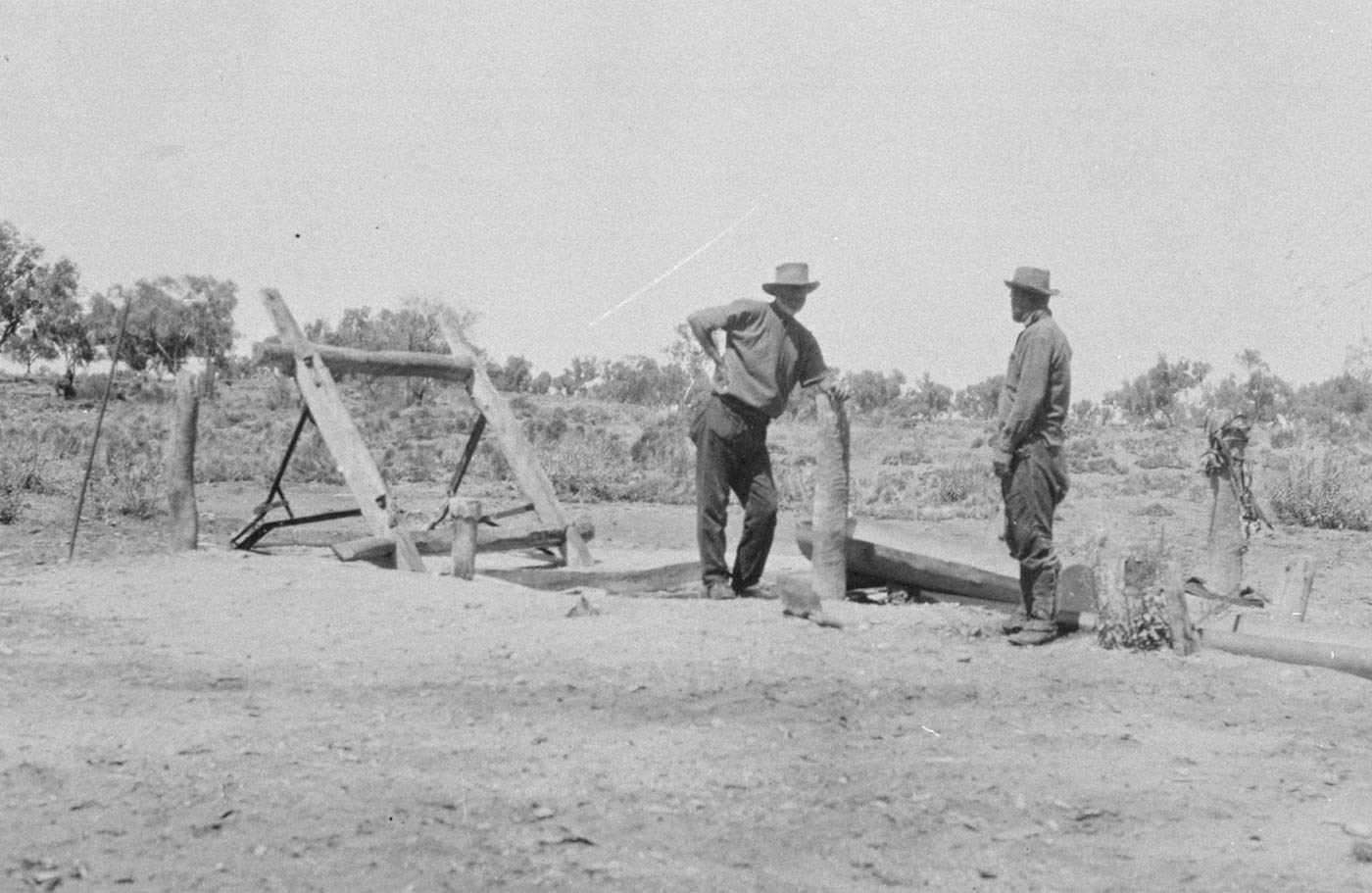 Black and white photo of two men standing in a rural setting adjacent to a wooden structure fabricated from logs.