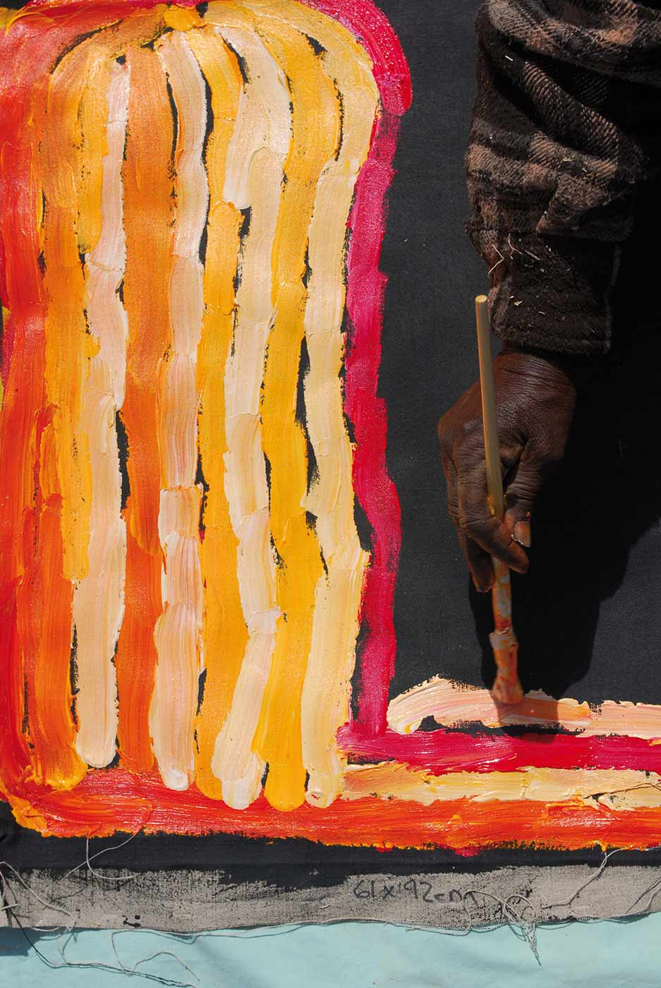 Colour photo of a hand painting pigment onto a canvas .  - click to view larger image