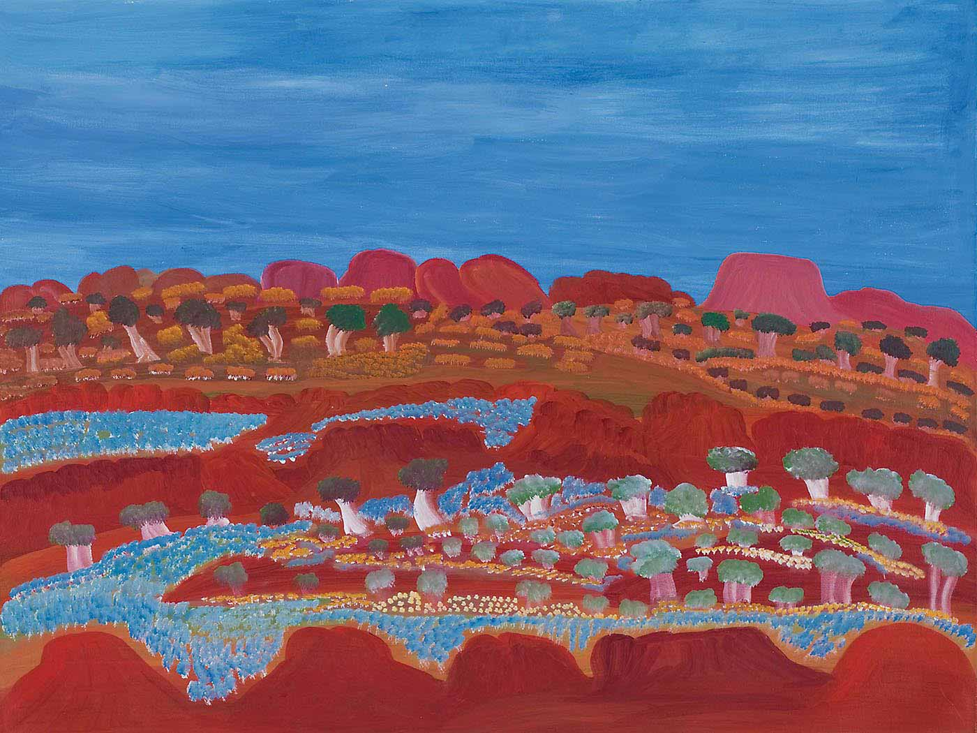 A painting on canvas with a range of orange-red rock formations lying low against a blue sky backdrop. In front of the formations are green and light brown trees and yellow-brown grass-like foliage. In the foreground are two horizontal rows of orange-red rock formations creating a valley-like appearance. The valley and some of the rock formations are covered in expanses of flowers in blue, yellow and cream as well as trees in green and beige-white. - click to view larger image