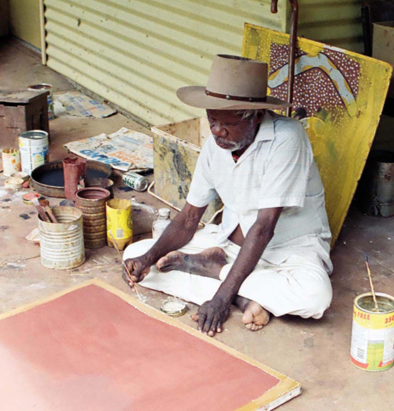 Colour photograph of a man sitting on the ground and painting.
