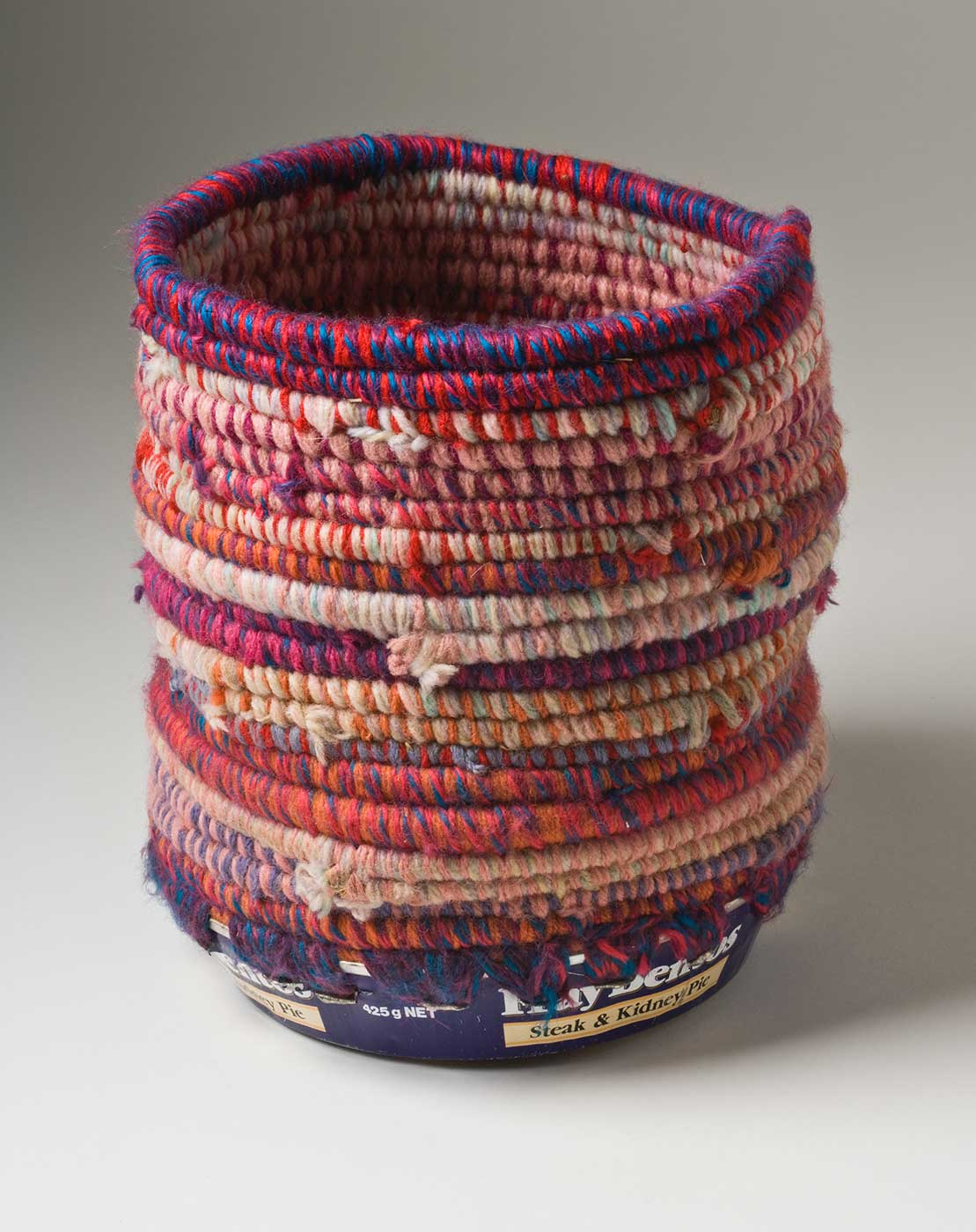 A cylindrical coiled multicoloured yarn and plant fibre basket with a metal base. The coiled yarn is in colours of blue, orange, red and purple with a dominant colour of pink. The base of the basket is a blue and white coloured metal tin with burn marks to the bottom which includes the text 'Fray Bentos / Steak and Kidney Pie'. Yarn is used to attach the base to the top section through holes that have been punched in the tin.