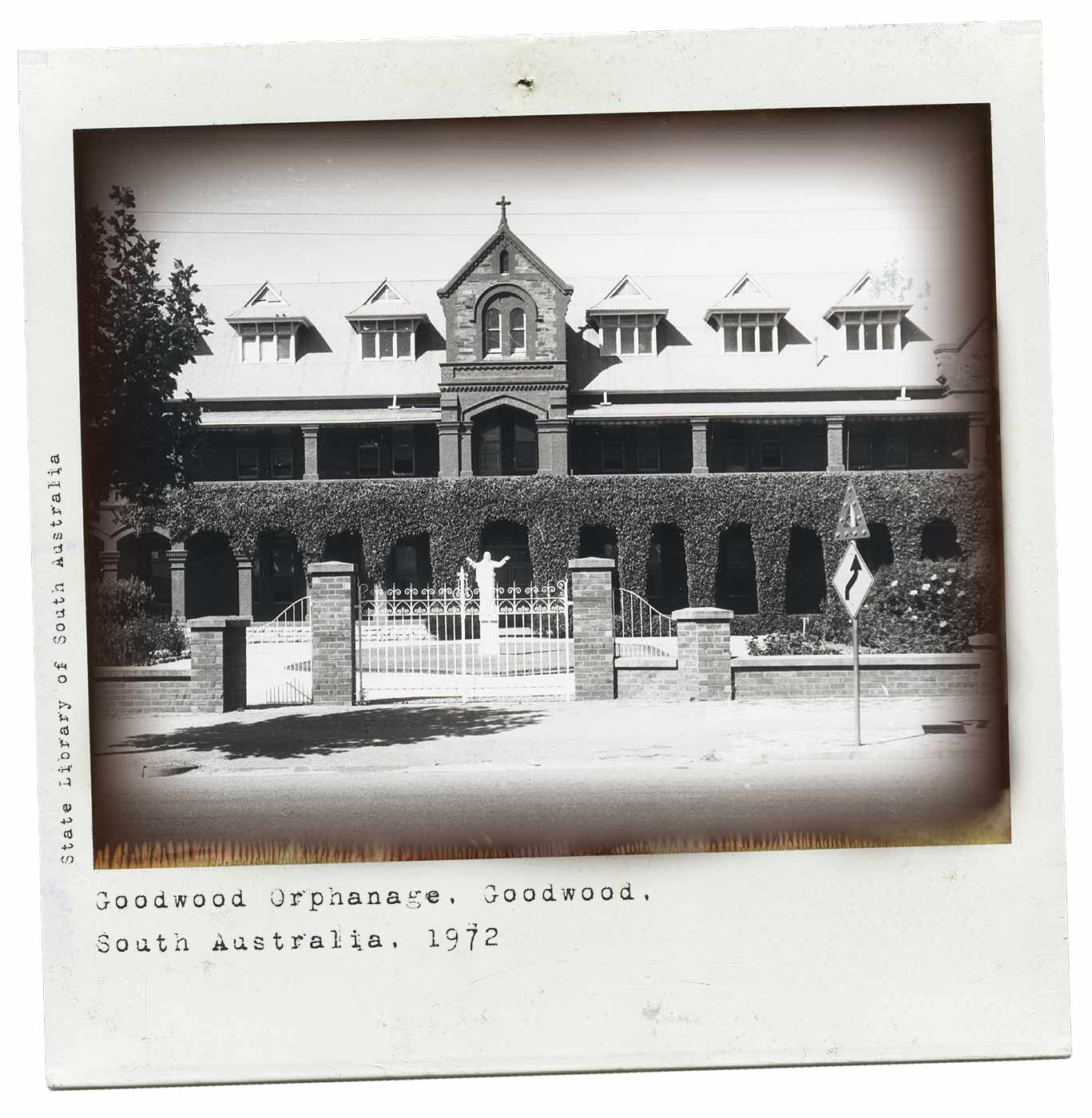 A black and white Polaroid photograph of a large building appearing to be of mid-1800s heritage. There is a white statue behind the main gate and a traffic sign to the right. Typewritten text underneath reads: 'Goodwood Orphanage. Goodwood. South Australia. 1972'. Up the left-hand side of the photo there is smaller text reading 'State Library of South Australia'. - click to view larger image