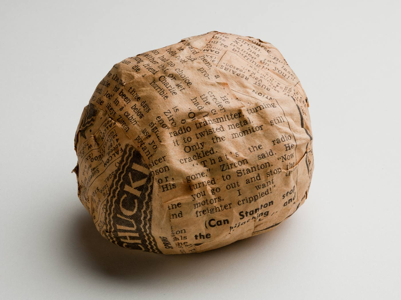 A rougly spherical ball wrapped in yellowing newspaper strips. - click to view larger image