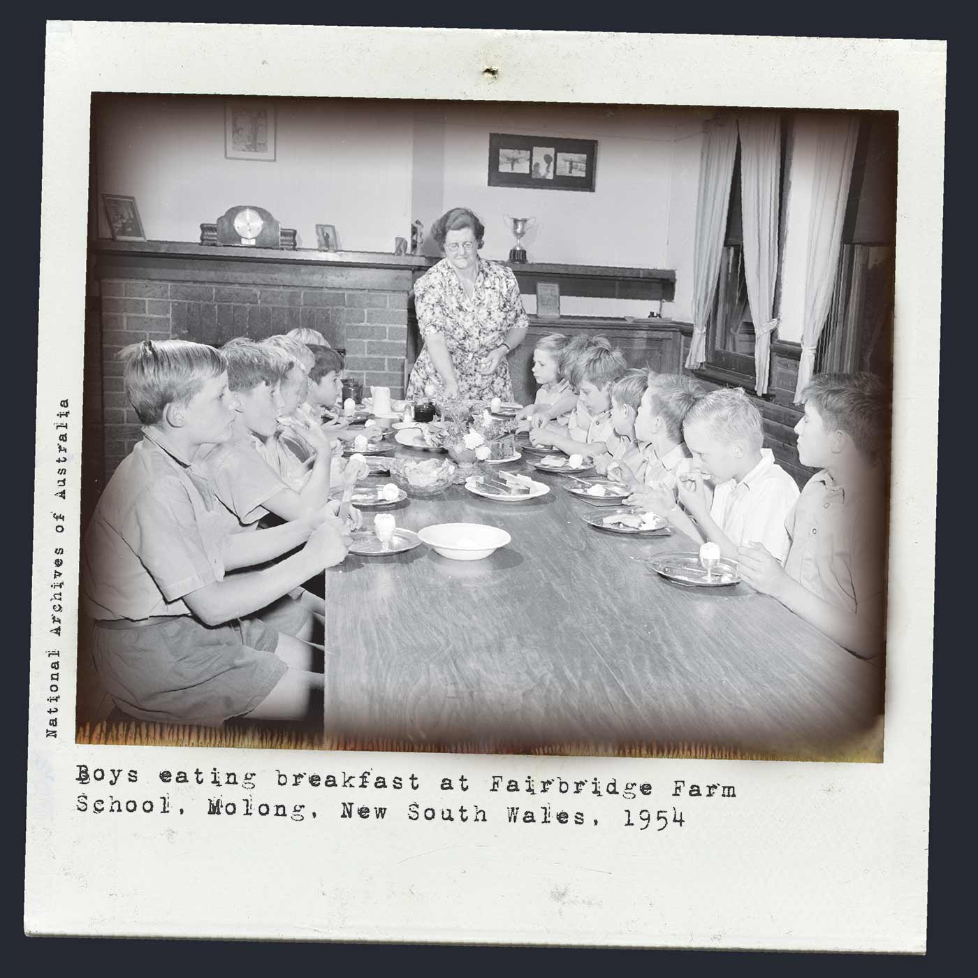 An image of a black and white Polaroid photo of boys sitting around a table eating a meal. There is a middle-aged woman serving at the end of the table. Typewritten text below reads 'Boys eating breakfast at Fairbridge Farm School, Molong, New South Wales, 1954'. 'National Archives of Australia' is typed along the left side. - click to view larger image