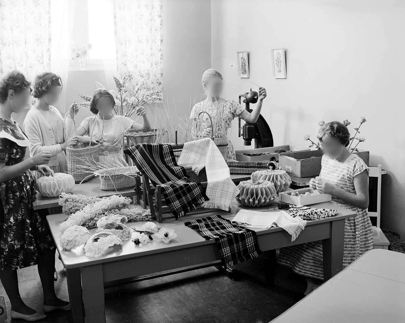 Black and white photos showing five teenage girls gathered around two tables covered with craft items. Three of the girls stand behind the tables working on baskets, a fourth at left working on a small cylindrical object, and a fifth, at right, seated at the table. - click to view larger image