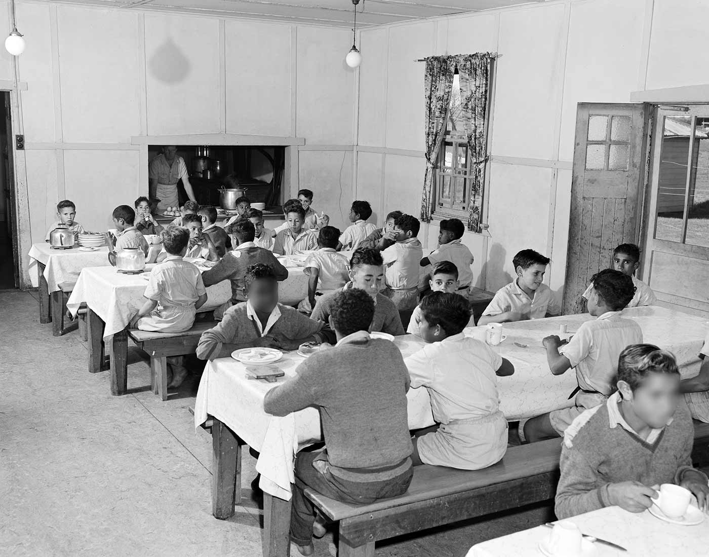 Black and white photo showing groups of young boys seated on long wooden benches at long tables, covered with white tablecloths. An adult stands at a servery window at the far end of the room. - click to view larger image