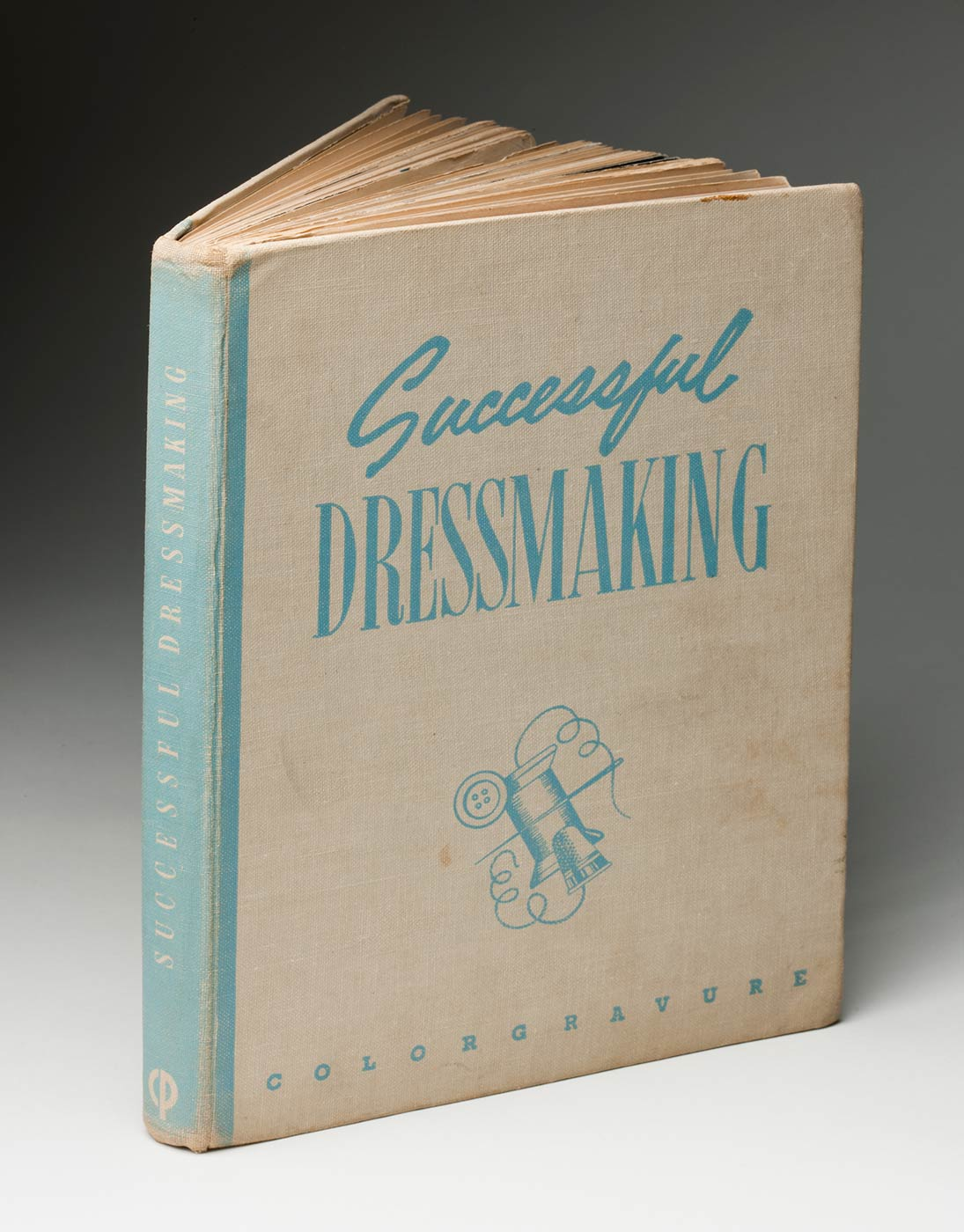 Beige and pale blue book cover titled 'Successful DRESSMAKING', with a line drawing of a needle, thread, button and thimble. - click to view larger image