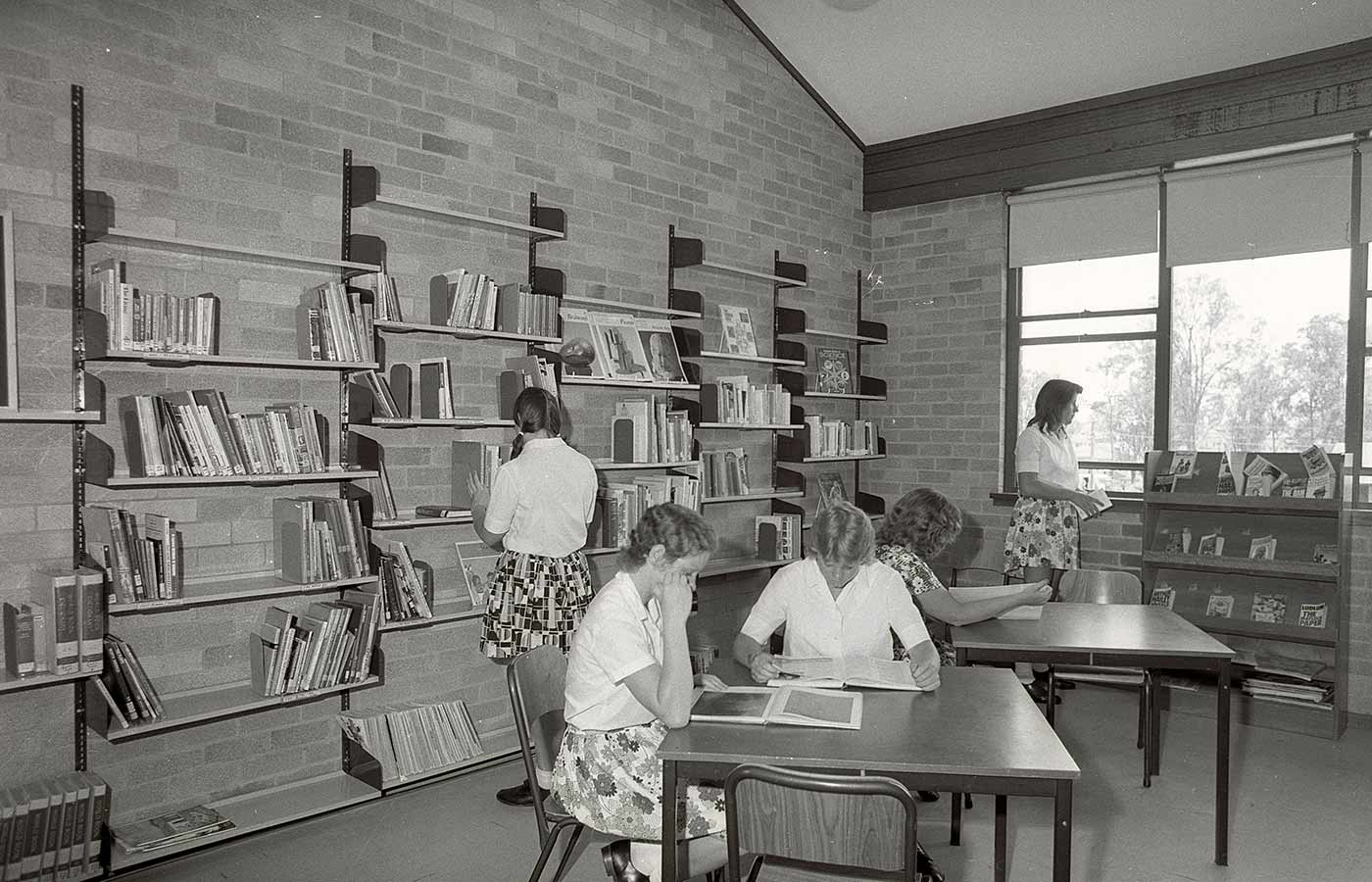 Black and white photo showing five teenage girls in a library. Three sit at tables, reading. Another girl browses at books on a shelf on the rear wall. A fifth girl stands looking out a window. - click to view larger image
