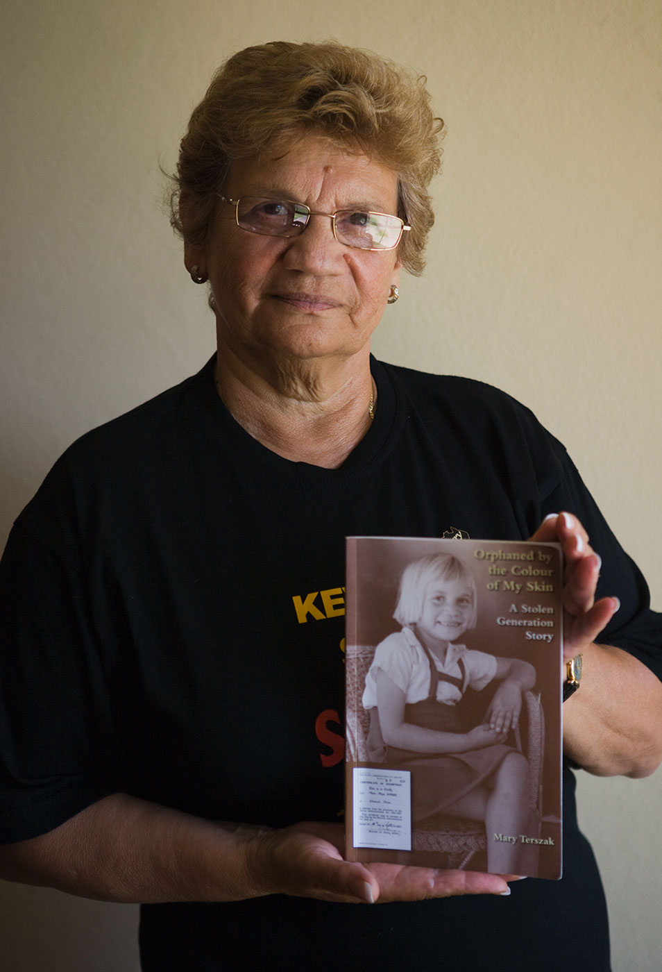 Colour photograph showing a woman holding a book in both hands. The book cover shows a photo of the woman as a young girl. - click to view larger image