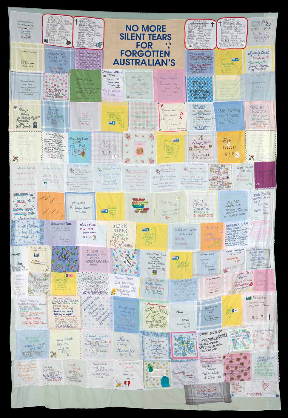 A colour photograph of a patchwork quilt made up of various coloured handkerchieves stitched together. The individual handkerchiefs have personal messages written and embroidered on them.