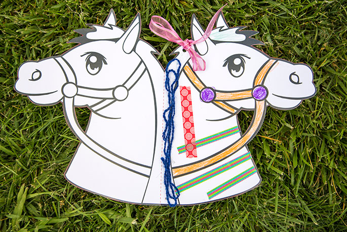 A paper template of a horse's head which has been folded in half so that there is a head on either side.  One side has been decorated.