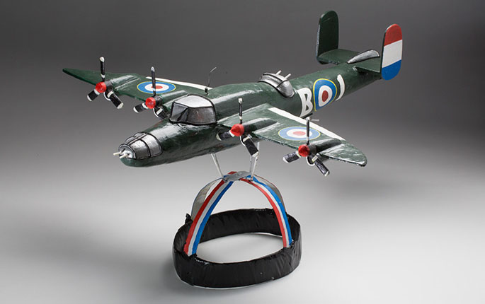 An aeroplane headdress modelled on a British Mitchell Carrier plane, circa WWII. The metal headpiece is painted in red, white and blue stripes, with black adhesive tape wrapped around the outer band. On top of the metal headpiece, is a painted wooden model of a British Carrier Plane, possibly made of balsa wood, supported by metal struts under the wings. The aeroplane is painted green with markings in blue, red, white and yellow. The wings each feature a target or bullseye design, and two propellers.