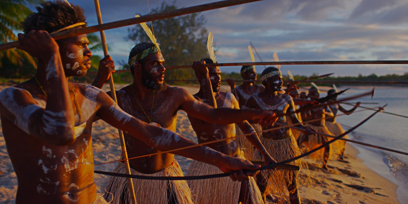 A group of warriors holding spears and ready to attack as they look out from a beach. They wear grass skirts and white feather headdresses.