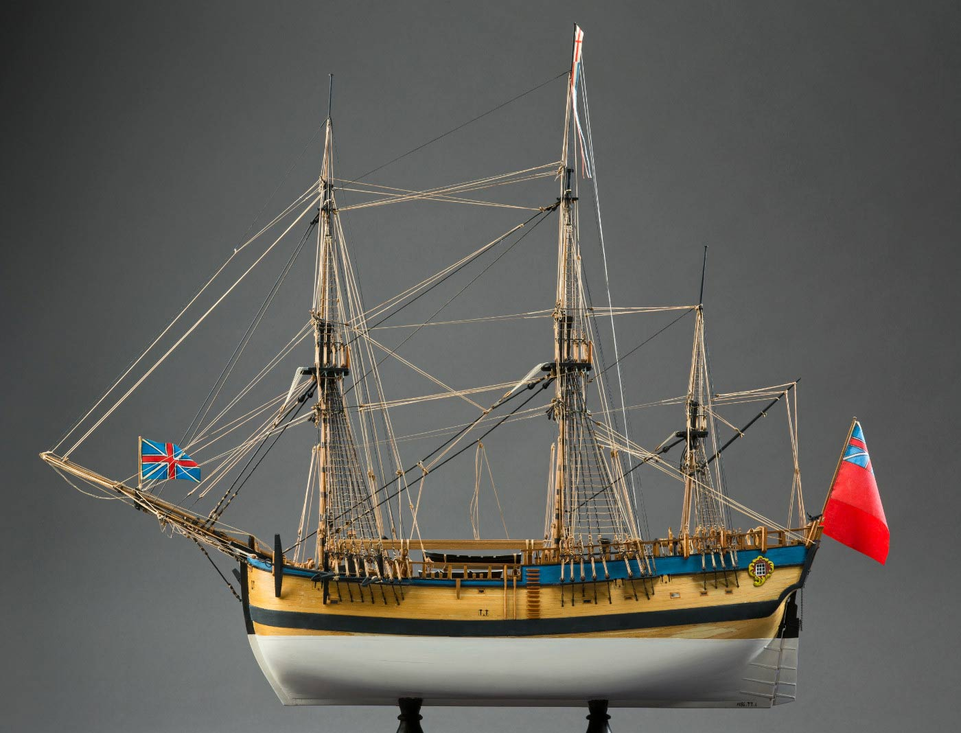 Side view of a model wooden sailing ship with a red flag at the rear. - click to view larger image
