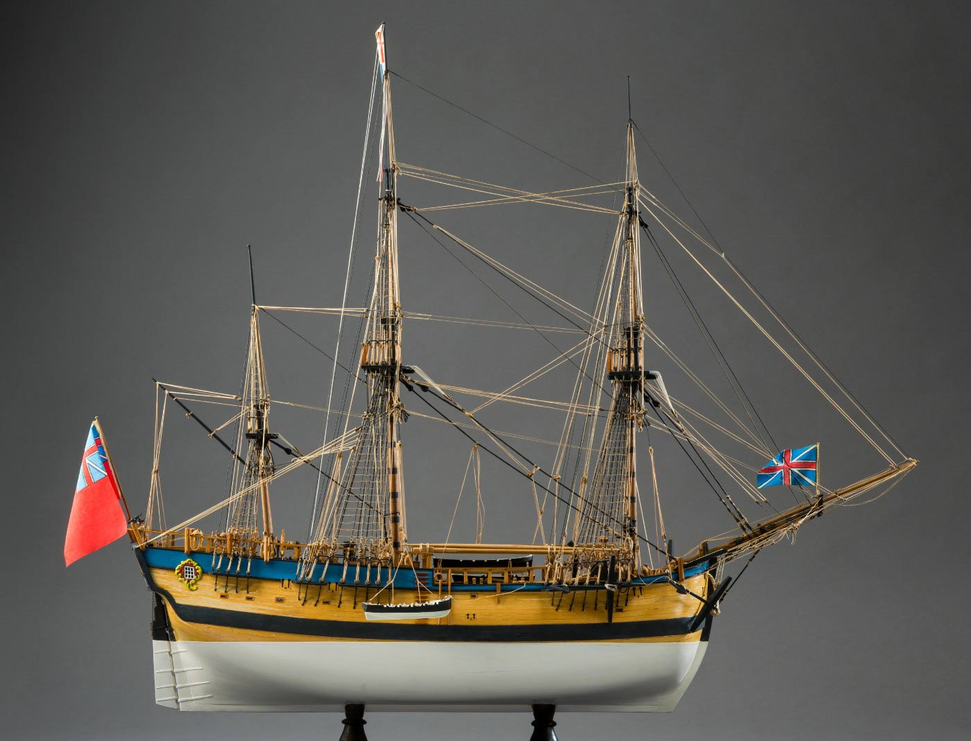 Side view of a model wooden sailing ship with a small boat partially lowered over the side. - click to view larger image