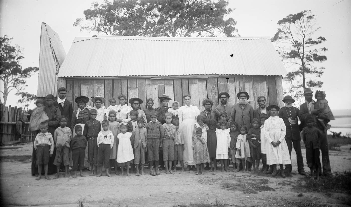 Black and white photograph showing a group of Aboriginal men, women and children standing in front of a slab hut.