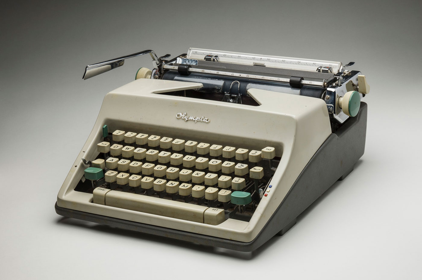 A metal and plastic 'Olympia' brand typewriter with an attached case. The typewriter has a grey plastic base and a bone coloured body with green turning knobs. 'OLYMPIA WERKE AG. WILHELMSHAVEN / Made in Western Germany' is written on a silver plaque screwed to the back of the typewriter. - click to view larger image