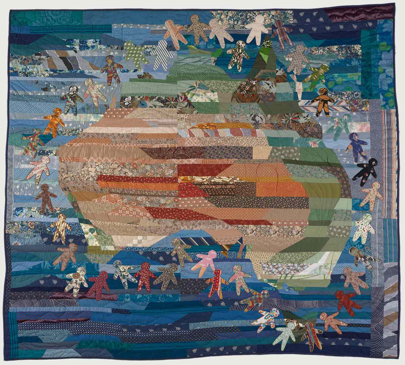 Colour photo of a patchwork quilt featuring human figures surrounding the Australian continent. - click to view larger image