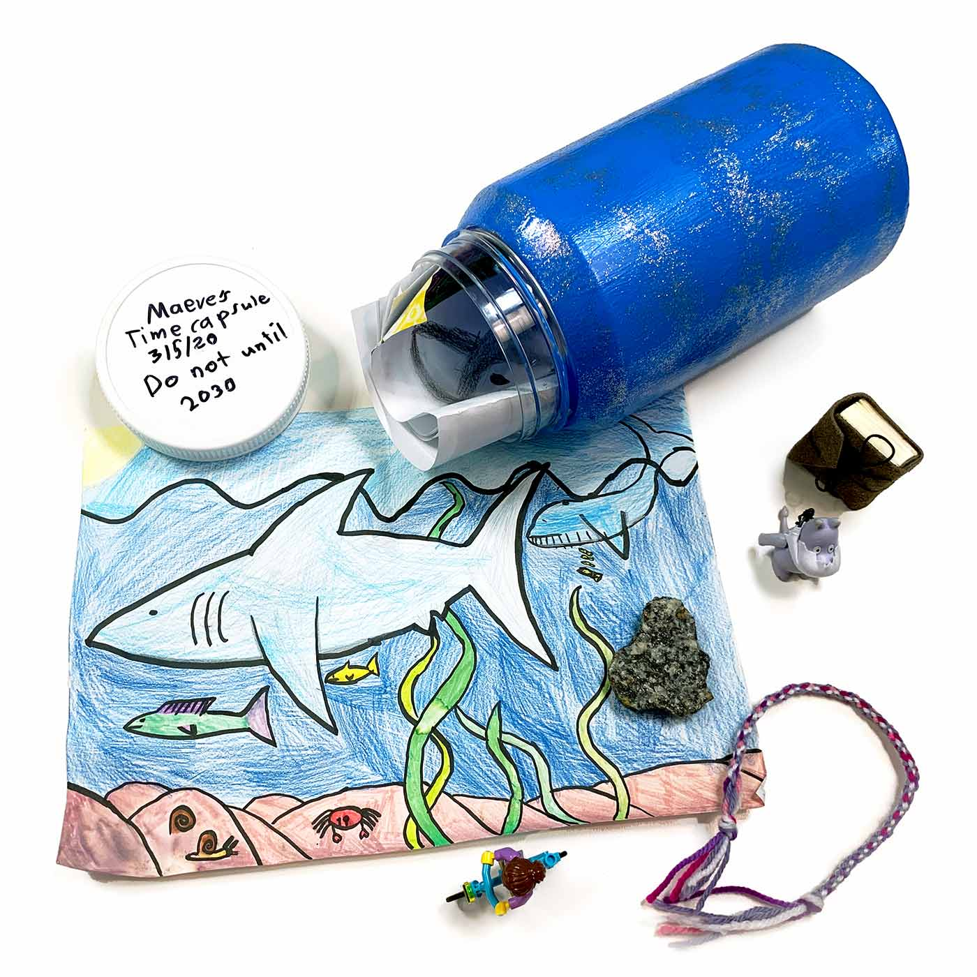 "Time capsule featuring a bottle with folded drawings on paper inside. The bottle is sitting next to other objects including a miniature diary, a Lego person on a bike, and a rock. These objects are sitting on top of a drawing featuring an underwater ocean scene. On top of the bottle's cap is written in black marker: ""Maeves Time capsule. 3/5/20. Do not until 2030"". - click to view larger image"