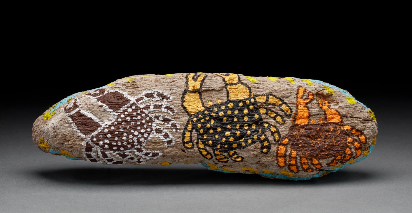 An acrylic painting on driftwood, featuring three crab like creatures each in its own colour combination of brown and yellow, black and yellow, and brown and white. - click to view larger image