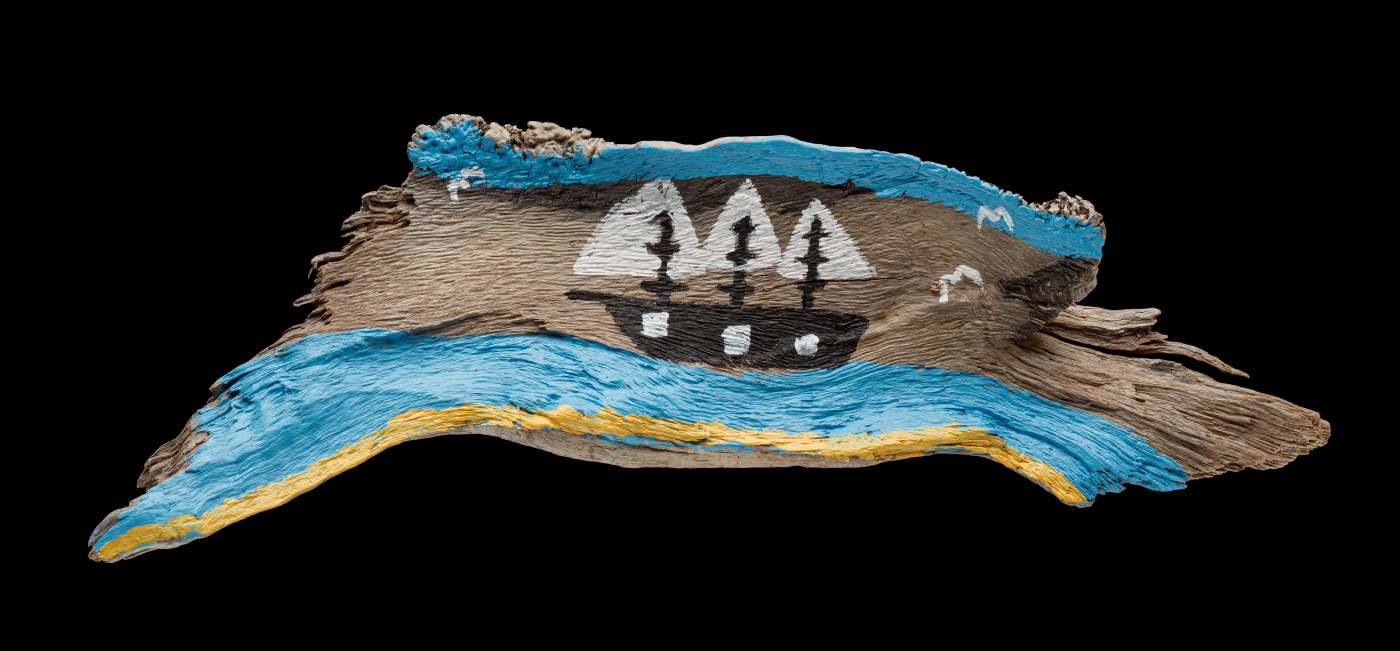 An acrylic painting on driftwood featuring a black boat with white sails, a yellow stripe representing the sand, blue stripes above and below the boat as water and the sky, and three white birds. - click to view larger image