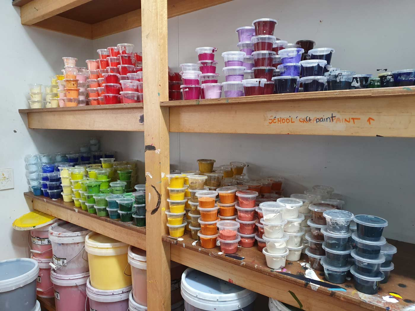 Colour photo of a large supply of coloured pigments on a shelf. - click to view larger image