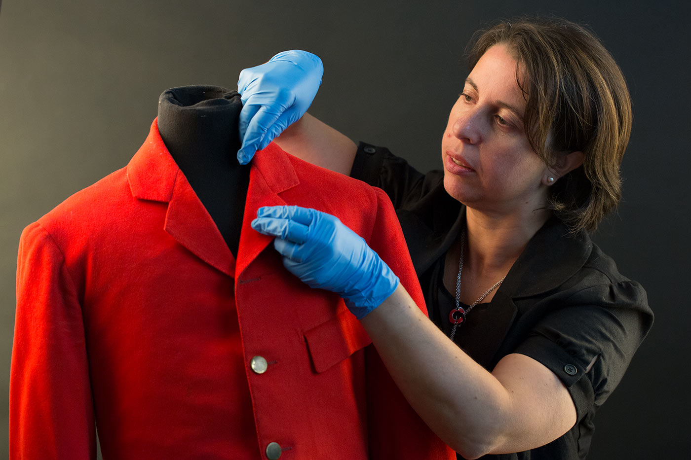 A woman is examining a red coat. - click to view larger image
