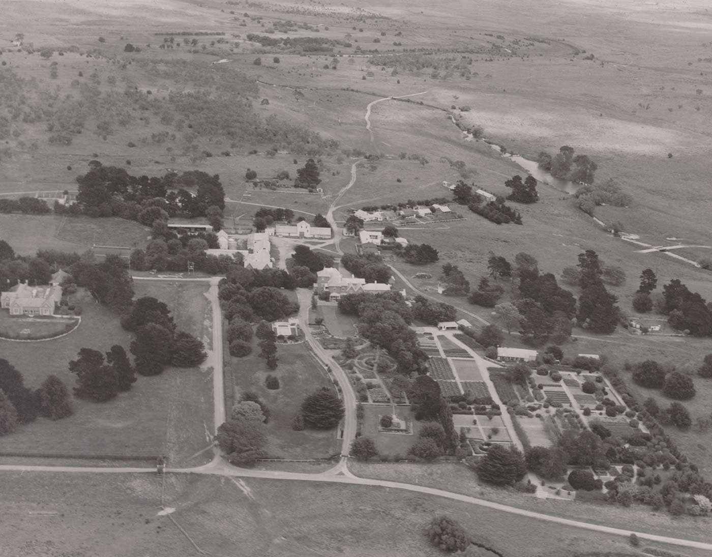 Black and white aerial photo of Springfield, showing several large buildings at centre, with formal gardens in the foreground and a small watercourse and paddocks behind.