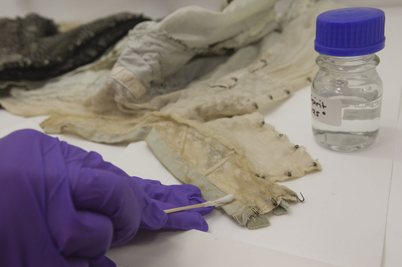 Conservator using a cotton bud to treat fabric in a laboratory. - click to view larger image