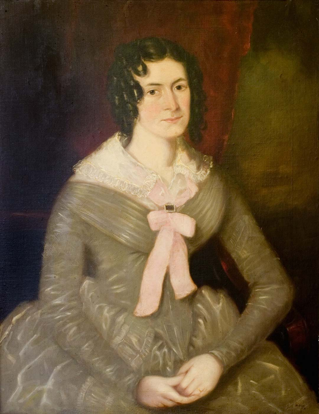 Portrait of a lady in 1845 seated with her hands folded together in her lap, with ringlets around her face wearing an olive-coloured dress with full skirt, tight waist and lace collar tied with pink bow and clasp at the front. - click to view larger image