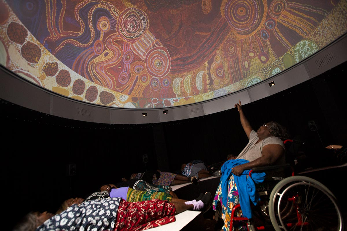 Colour photo of people viewing visual projections on a large dome above.