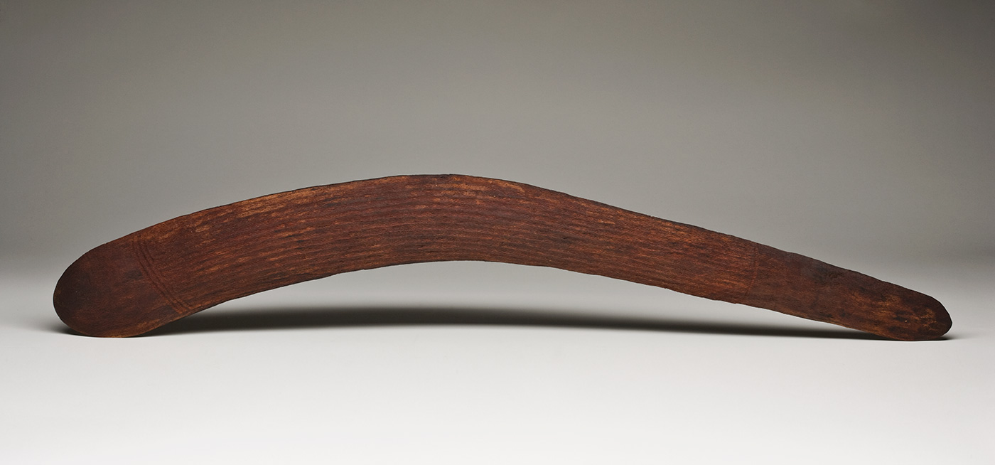 An asymmetrical dark brown wooden boomerang with incised decoration on both sides. The boomerang is slightly convex on one surface and almost flat on the other. One end is semicircular while the other is a narrower rounded point. Both sides have three sections of parallel horizontal grooves. On the convex surface there are three grooves at the larger end, seven grooves at the centre and two grooves at the narrower end. On the flat surface there are three curved grooves at the larger end, six grooves at the centre and three grooves at the narrow end. - click to view larger image