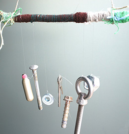 A set of chimes made from a stick wrapped in wool and string that has a variety of bolts and screws dangling from it.