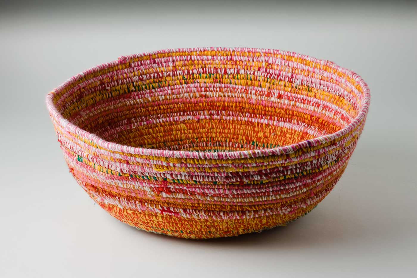 An oval coiled multicoloured yarn and plant fibre basket. The plant fibre in the centre of the basket is covered by brown-blue yarn, followed by horizontal alternate yarn coverings over the fibre. The yarn colours are green-yellow, red-yellow, red-white, red-green, green-white, pink-white, red-brown, pink-brown, and yellow pink. The top plant fibre is covered by pink-white yarn.