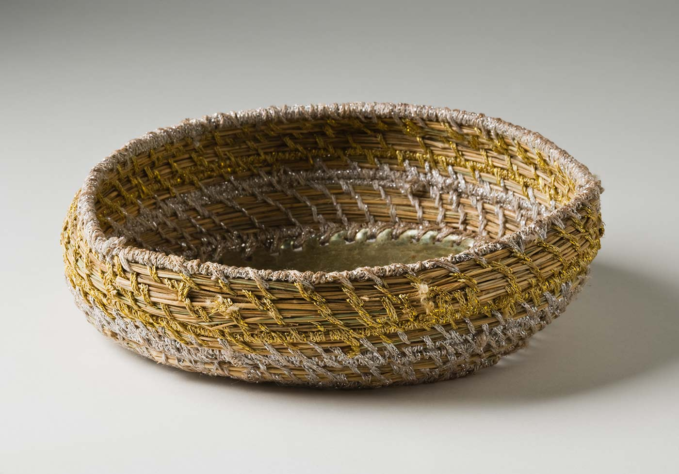 A shallow circular metallic yarn and plant fibre basket with metal base. The base is made of a blue 'Fray Bento / Steak and Kidney Pie' tin lid which has been attached to the yarn section with silver coloured metallic yarn through holes punched in the tin. The basket has silver and gold coloured metallic yarn spaced out so the plant fibre centre can be seen. - click to view larger image