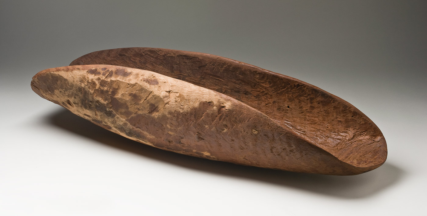 A red-brown wooden concave oval container with dark patches on the sides of the outer surface. The inner surface is rough with the tool marks and there are short parallel grooves along one end of the inner surface. The outer sides are a light beige colour. - click to view larger image