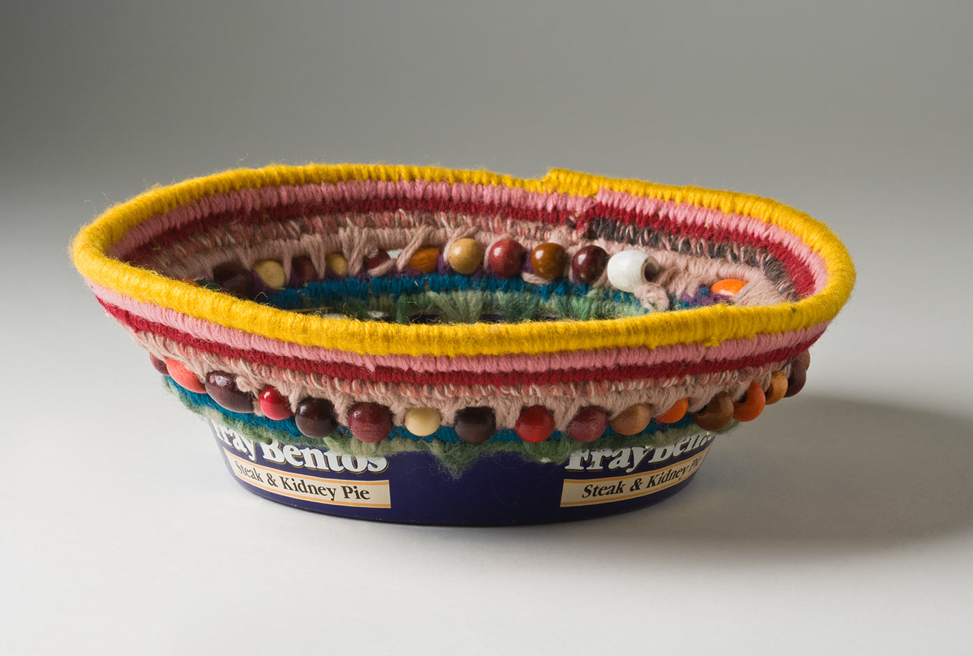 A circular coiled striped yarn basket over plant fibre with bead decoration, which opens out towards the top and has a metal base. The base of the basket is a blue and white coloured metal tin with burn marks to the bottom which includes the text 'Fray Bentos / Steak and Kidney Pie'. Yarn is used to attach the base to the top section through holes that have been punched in the tin. The basket has a stripe of yellow at the top edge followed by pink, dark pink, brown and mid pink, peach, teal and light green. Multicoloured oval and round wood beads are attached within the yarn coils at the top of the metal base. - click to view larger image